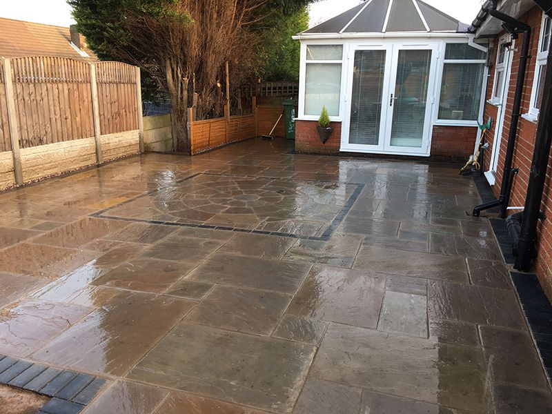 Autumn brown Indian stone flagged patio with charcoal boarder. New fencing Leigh